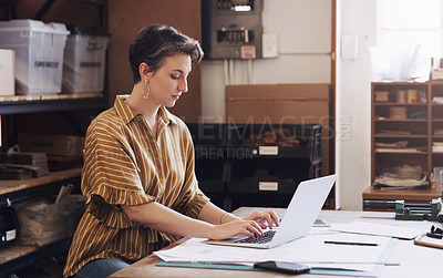 Buy stock photo Shot of a businesswoman using a laptop while designing a blueprint in a creative office