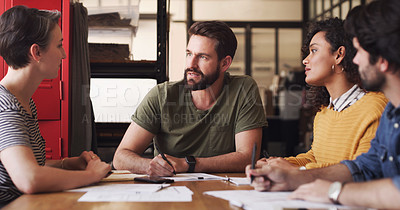 Buy stock photo Shot of a group of young businesspeople having a meeting in a creative office