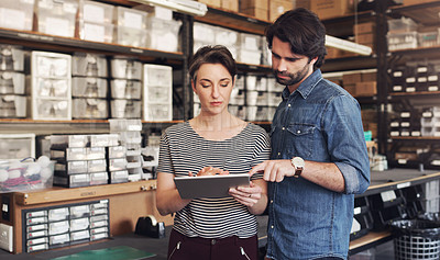 Buy stock photo Shot of a businessman and businesswoman using a digital tablet in a creative office