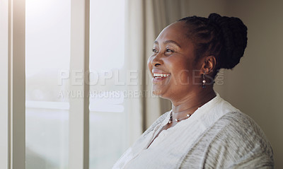 Buy stock photo Cropped shot of a happy senior woman standing alone in her home and looking out of her window