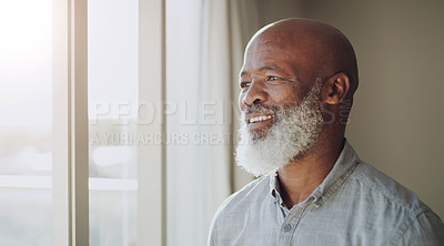 Buy stock photo Cropped shot of a happy senior man standing alone in his home and looking out of his window