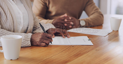 Buy stock photo Cropped shot of an unrecognizable woman signing a document in her home during the day