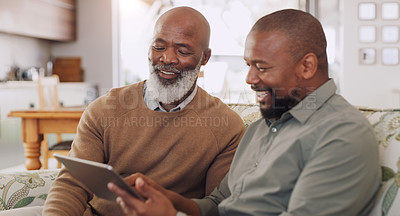 Buy stock photo Cropped shot of a happy young man sitting with his senior father and using a tablet in their living room