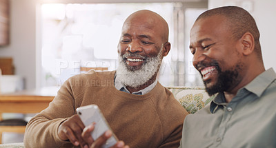 Buy stock photo Cropped shot of a happy young man sitting with his senior father and using a cellphone in their living room