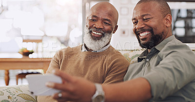 Buy stock photo Cropped portrait of a happy young man sitting and using a cellphone to take a selfie with his senior father in their home
