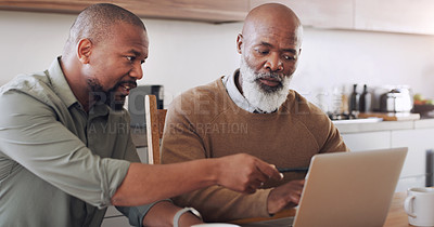 Buy stock photo Cropped shot of a handsome young man sitting with his senior father and using a laptop in their home