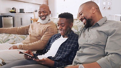 Buy stock photo Cropped shot of a young boy sitting on the sofa with his father and grandfather while using a tablet
