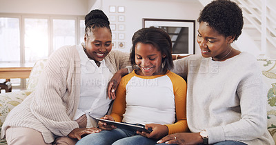 Buy stock photo Cropped shot of a young girl sitting on the sofa with her mother and grandmother while using a tablet