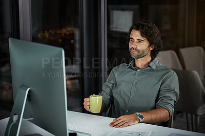 Buy stock photo Cropped shot of a handsome young businessman working on a computer inside his office at night
