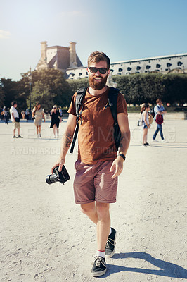 Buy stock photo Shot of a man holding his camera while exploring a foreign city