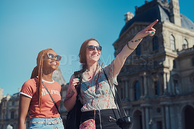 Buy stock photo Cropped shot of two female friends exploring a foreign city together