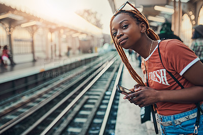 Buy stock photo Cropped shot of a young woman using her cellphone while waiting for the train