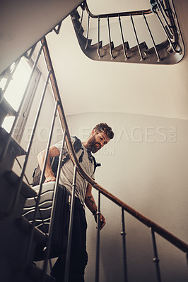 Buy stock photo Shot of a young man walking down a staircase with his luggage
