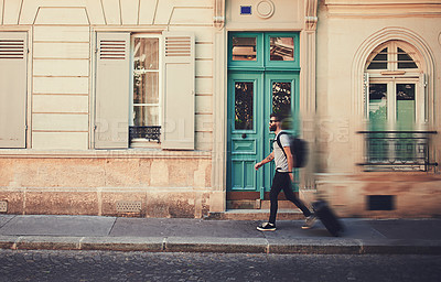 Buy stock photo Shot of a man walking with his luggage through a foreign city