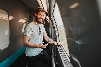 Buy stock photo Cropped shot of a man using his cellphone while standing by the window in a train