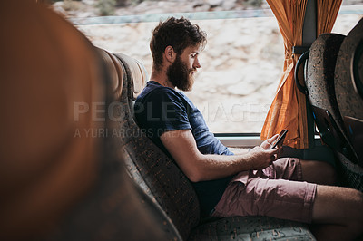 Buy stock photo Shot of a handsome young man using his cellphone while sitting on the bus