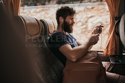 Buy stock photo Shot of a man listening to music through his cellphone while sitting on the bus
