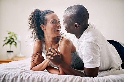 Buy stock photo Cropped shot of an affectionate young couple smiling at each other while lying on their bed at home