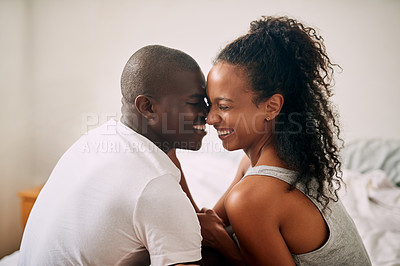 Buy stock photo Cropped shot of an affectionate young couple sharing an intimate moment in their bedroom at home