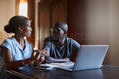 Buy stock photo Cropped shot of a young couple sitting together and using a laptop in their living room during a day off