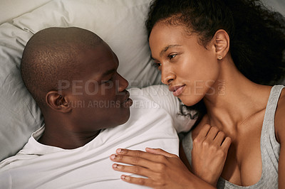 Buy stock photo High angle shot of an affectionate young couple sharing an intimate moment while lying in bed at home