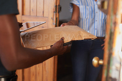 Buy stock photo Cropped shot of an unrecognizable woman accepting a parcel from a delivery man during a day off at home