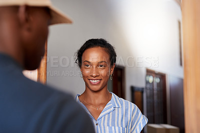 Buy stock photo Cropped shot of an attractive young woman accepting a parcel from a delivery man during a day off at home