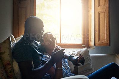 Buy stock photo Cropped shot of an affectionate young couple cuddling on the sofa together during a day at home