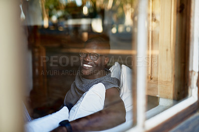 Buy stock photo Cropped portrait of a handsome young man sitting alone on the sofa during a day off in his home