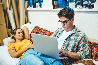 Buy stock photo Shot of a cheerful young couple browsing on a laptop together while being seated on a sofa inside at home