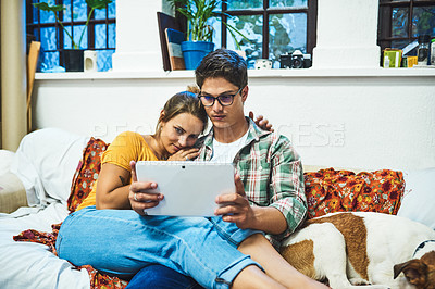 Buy stock photo Cropped shot of a cheerful young couple browsing on a digital tablet together while being seated on a sofa inside at home