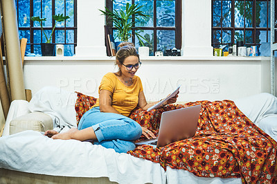 Buy stock photo Shot of a cheerful young woman browsing on a laptop while doing paperwork on her bed at home during the day