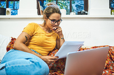 Buy stock photo Cropped shot of a cheerful young woman browsing on a laptop while doing paperwork on her bed at home during the day