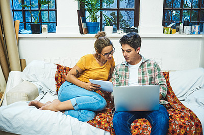 Buy stock photo Cropped shot of a cheerful young couple browsing on a laptop while doing paperwork on a sofa at home during the day