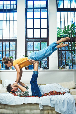 Buy stock photo Shot of a cheerful young man lifting his girlfriend in the air with his legs and arms while lying on his back on a sofa at home