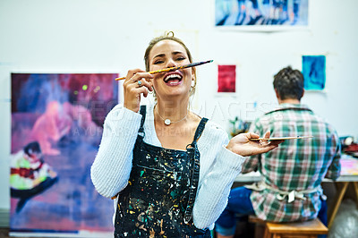 Buy stock photo Cropped portrait of an attractive young female painter making a face using a paintbrush in an art studio
