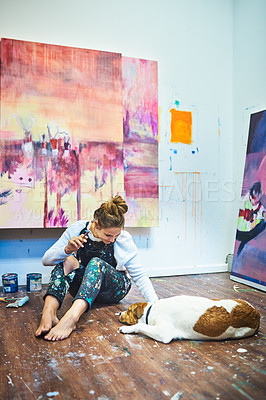Buy stock photo Full length shot of an attractive young female painter playing with her dog while sitting on the floor in her art studio