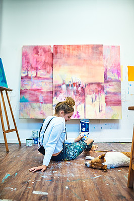 Buy stock photo Full length shot of an attractive young female painter admiring her sleeping dog while sitting down on the floor in an art studio
