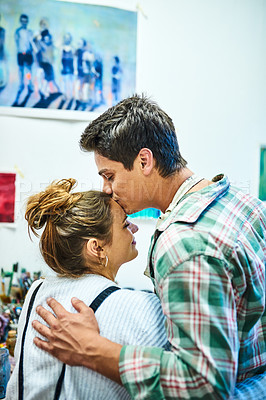 Buy stock photo Cropped shot of an affectionate young man kissing his girlfriend on the forehead in an art studio