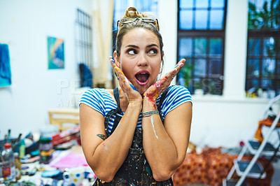 Buy stock photo Cropped shot of an attractive young female painter looking shocked while standing in her art studio