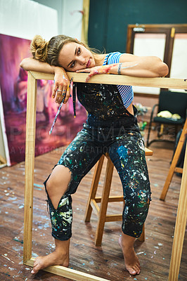 Buy stock photo Full length shot of an attractive young female painter looking sad while leaning on a wooden frame in her art studio
