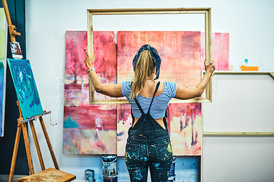 Buy stock photo Rearview shot of an unrecognizable woman standing alone and holding a wooden frame in her art studio