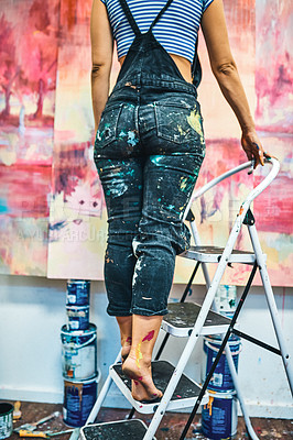 Buy stock photo Cropped shot of an unrecognizable woman standing on a ladder to paint in her art studio