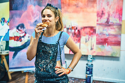 Buy stock photo Cropped portrait of an attractive young woman standing alone and eating a slice of pizza in her art studio