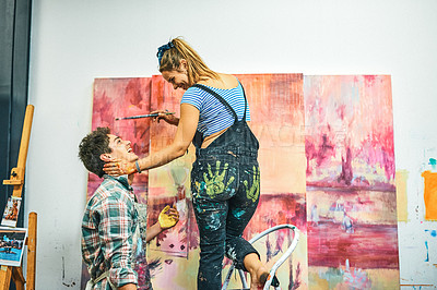 Buy stock photo Cropped shot of an affectionate young couple feeling playful during a painting session in the studio