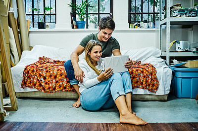 Buy stock photo Full length shot of a happy young couple using a digital tablet while spending time together at home