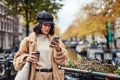 Buy stock photo Shot of a beautiful young woman using a smartphone and having coffee in the city