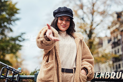 Buy stock photo Shot of a young woman extending her hand to you in the city