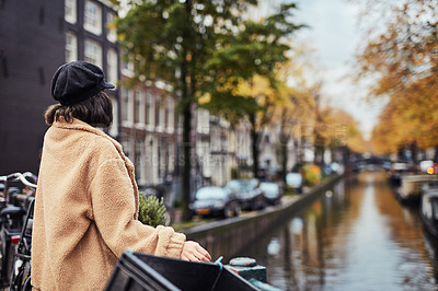 Buy stock photo Rearview shot of a young woman looking at a canal in the city
