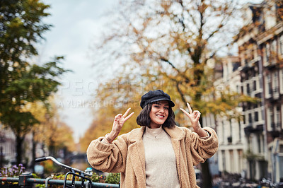 Buy stock photo Shot of a beautiful young woman making a peace gesture in the city